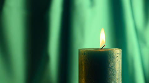 Teal candle trembling flame with green curtain background Footage