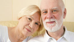 Portrait of cheerful good-looking senior couple sitting on sofa at home. Having Footage