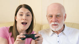 Father and daughter gamers playing video game at home.Players with remote ビデオ