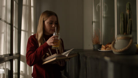 Intelligent young woman reading a book at home Live Action