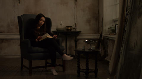 Cute asian woman reading a book in retro interior Live Action