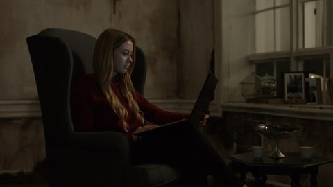 Charming young woman using laptop in the evening Live Action