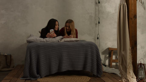 Diverse girls lying on bed texting on phones Live Action