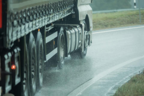 A truck is driving on the road in the rain Fotografía