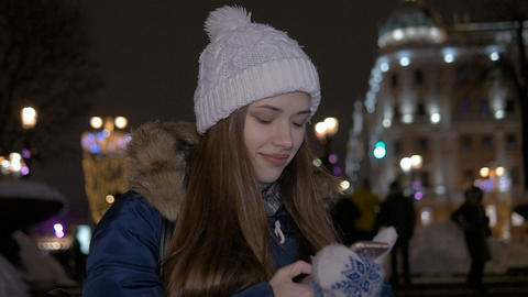 Slow motion. The girl writes sms on the smartphone. In the street in winter, in Footage