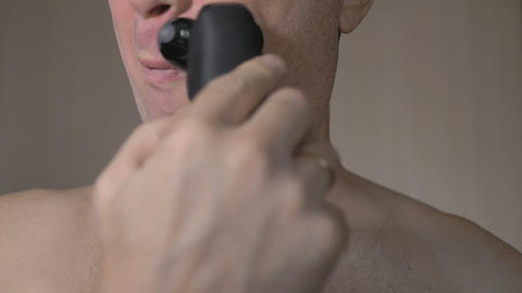 The man shaves his face with an electric razor. It is very much covered with Footage