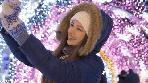 A young girl does selfie on a smartphone. Against the background of festive 画像