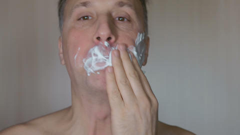 A man smears his face with shaving foam. Close-up Footage