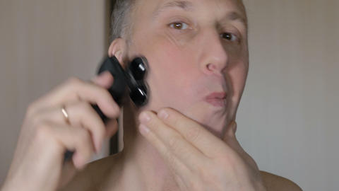 The man is shaving his face cleanly with an electric razor. Closeup Footage