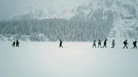 Low altitude aerial shot of unrecognizable people hiking on the snowy lake Footage