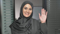 A young Arab girl in a hijab waving her hand, a gesture of greeting, hi, hello Footage