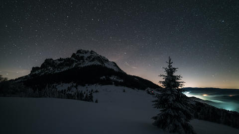 Night sky with stars moving over mountain peak in winter astronomy time lapse Footage
