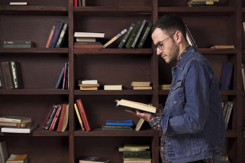 Young man reading a book in the library Foto
