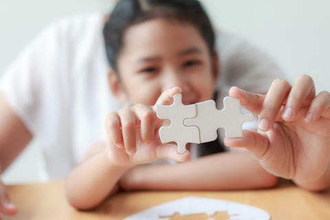 Asian little girl playing jigsaw puzzle with her mother for fami フォト