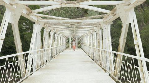 Young girl walks on the suspension bridge - Georgia ビデオ