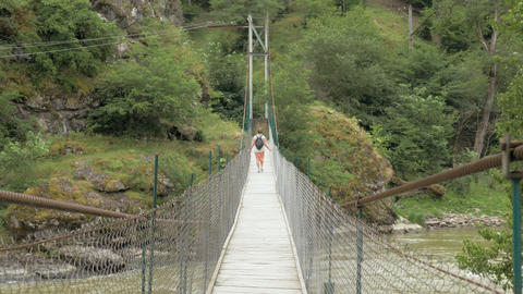 Young girl walks on the suspension bridge - Georgia Archivo
