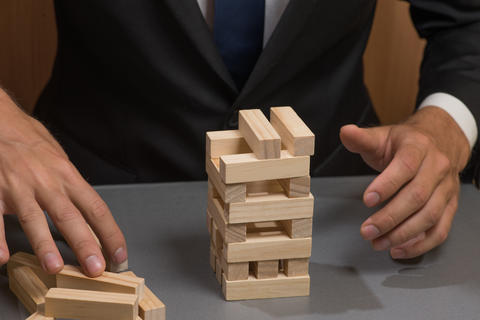 Wooden tower blocks, the hand of the businessman. Risks and planning フォト