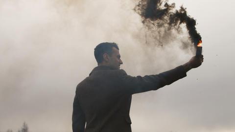 Serious man holding smoke bomb with black fume Bild