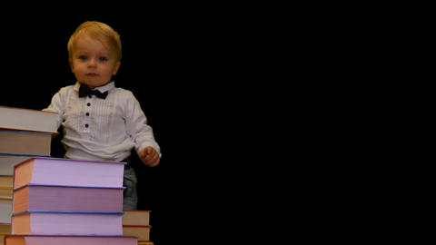 cute 1 year baby supports on pile of books on black background Footage