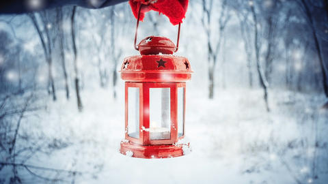 Holding in red glove a red candle lantern in the winter forest Footage
