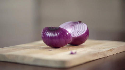 Close-up of professional cook chopping onion in half on cutting board Live Action
