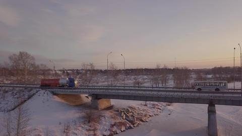 Gasoline truck moving along bridge over frozen river against winter landscape Footage