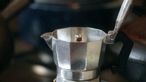 Italian coffee is ready in the moka cofeepot. A man's hand takes a coffee maker ビデオ