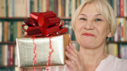 Senior woman with present. Pensioner holding golden gift box with red ribbon Footage