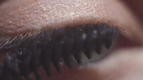 Green eyed female applying black make up mascara on eyelash Footage