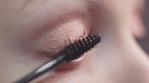 Green eyed woman puts black make up mascara on eyelash Footage