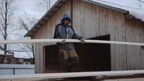 Porter carrying wood plank at sawmill factory yard on winter day Footage