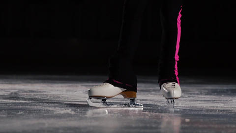 Close-up, legs in ice skates go to the ice and move in the frame. The camera Footage