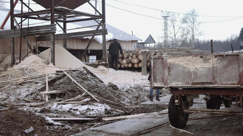 Blue tractor riding on dirty sawmill factory yard on winter day Footage
