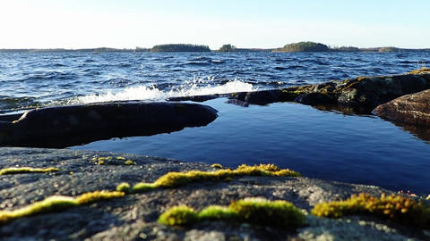 Waves splashing over a puddle at Nordic lake shore Footage