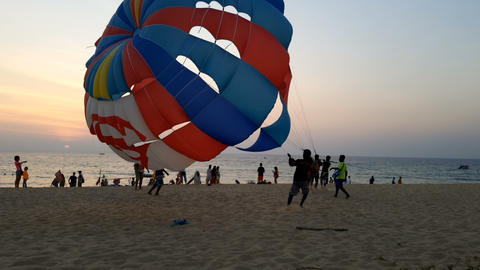 Tourists on parasailing at Karon beach in the evening 画像