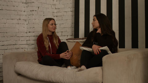 Relaxed diverse girlfriends chatting on the couch Live Action