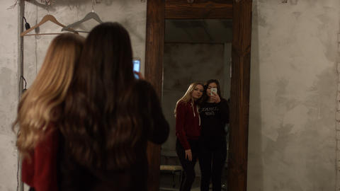 Reflection of cute girls taking selfie in mirror Image