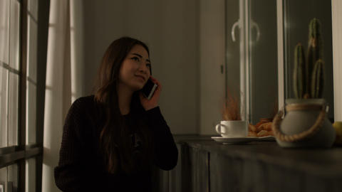 Joyful asian young woman chatting on cellphone Live Action