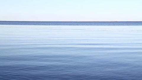 Waves and ripples run on blue water surface Footage
