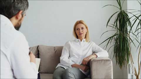 Male psychoanalyst listening adult female patient and writing notes in Footage