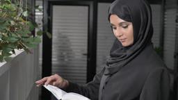 Beautiful young girl in black hijab stands at office and reads book. Looks at Footage