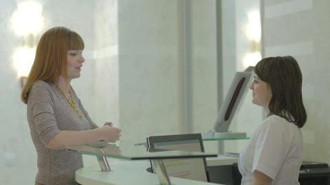 Patient and nurse conversing at hospital reception desk Footage