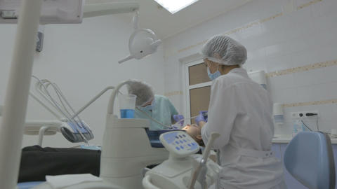 Dentist and dental assistant working on patient's teeth in a real dental surgery Footage