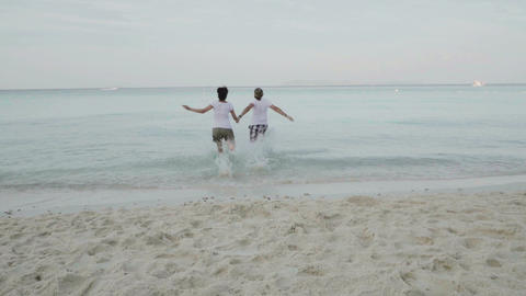 man and woman jumping into the sea Footage