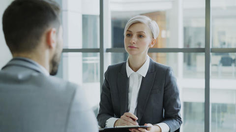 HR businesswoman having job interview with young man in suit and watching his Footage