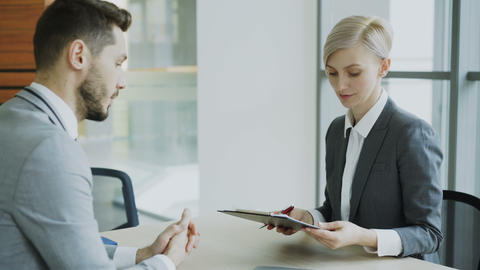Male colleague giving contract for signing to blonde businesswoman in suit and Footage