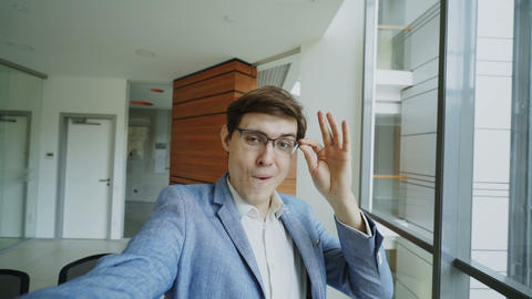 POV of young joyful businessman in glasses taking a selfie photo and have fun in Footage