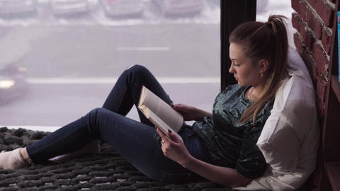 Young pensive woman reading book on bed by window overlooking city street ภาพวิดีโอ