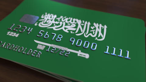 Plastic bank card featuring flag of Saudi Arabia. National banking system Footage