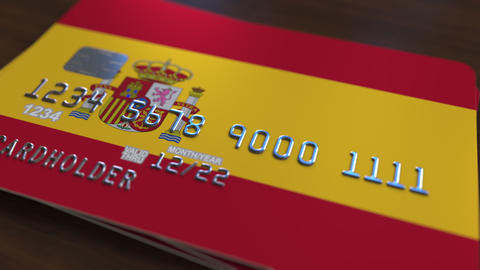 Plastic bank card featuring flag of Spain. National banking system related Live Action